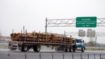 A truck carrying logs heads toward the Canada border. Reuters.